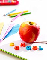 Close_up of an apple with plastic letters on a notebook
