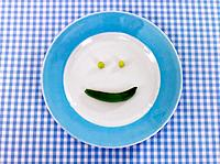 Close_up of green peas on a plate forming a smiley face