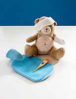 Close_up of a teddy bear with arm and head bandaged and medical equipments