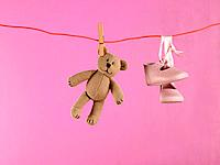 Close_up of a teddy bear and a pair of baby booties hanging on a clothesline