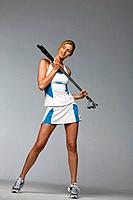 Young woman holding golf clubs, studio shot