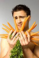 Close_up of young man holding carrots
