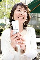 Mature adult woman using a mobile phone, Front View, Differential Focus