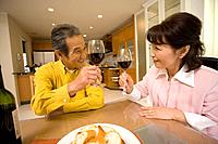 A Senior Adult Couple Toasting with Glasses of Red Wine, Front View, Side View
