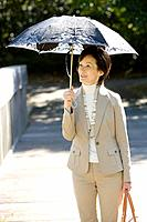 A Mature Woman Putting Up a Parasol, Front View, Three Quarter Length