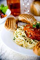 European and Italian food _ Pasta and salad on a white table cloth with garnish of bread with wine