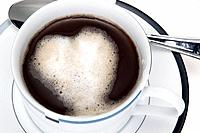 Foam heart on black coffee in white cup with spoon