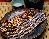 Closed Up Image of Several Pieces of Pickled Fish and Some Sake, High Angle View