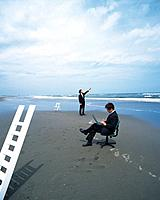 Image of Two Businessmen at the Beach, the One Using a Laptop, the Other One Pointing at the Sky, Far View, Side View
