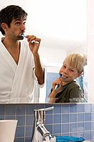 A father and son brushing their teeth