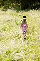 Rear view of children walking through long grass