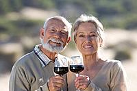 Senior couple toasting with red wine