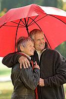 Senior couple using a red umbrella (thumbnail)