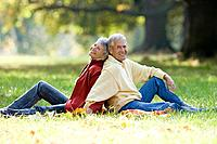 Senior couple sitting back to back in a park (thumbnail)