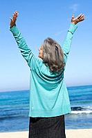 Senior woman with arms raised at the beach