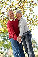 Senior couple dancing near a tree