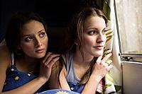 Two teenage girls looking out of a window