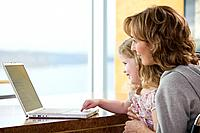 A mother and daughter using a laptop