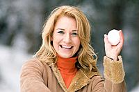 Austria, Salzburger Land, Altenmarkt, Young woman holding a snow ball, smiling, portrait