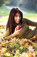Brunette woman relaxing on autumn foliage, portrait