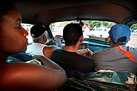 Men and a woman on a taxi in Havana, Cuba.