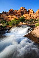 Snowmelt cascades over smooth sandstone below a rugged skyline near Moab, Utah, USA