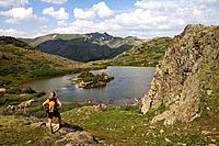 Female hiker pauses to take in the view above Highland Mary Lakes in the Weminuche Wilderness, San Juan Mountains, Colorado, USA