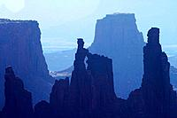 Washer Woman Arch and layers of sandstone cliffs backlit in early morning haze, Canyonlands National Park, Utah, USA