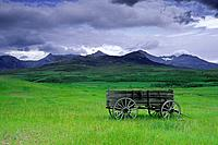 Old wagon and Rocky Mountains near Twin Butte, Alberta Canada
