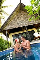 Couple ages 26 and 39 enjoying the refreshing dip pool at their private bure bungalow  Beautiful tropical resort holiday  Beqa Lagoon Resort, Beqa Isl...