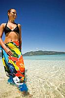 Woman age 23 in a colorful sulu sarong wrap standing in the clear tropical waters of a remote island near Beqa Lagoon, Beqa Island, Fiji