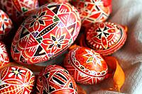 A half basket of  red hand-painted Czech Easter eggs. A large goose egg hand-painted in red and black abstract geometrical  pattern is  surrounded by ...