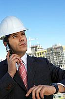 Businessman in hardhat using mobile phone outdoors