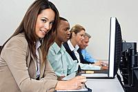 Group of business people using computers in classroom side view