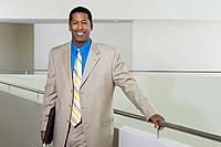 Business man standing by balustrade in office building portrait