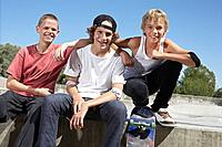 Three teenage boys 16_17 with skateboards at skate park portrait