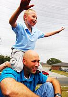 Boy climbing on his father´s back and laughing