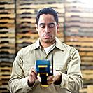Warehouse Worker Entering Data into Handheld Computer
