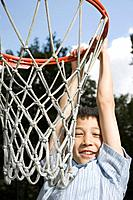 Asian boy hanging from basketball hoop