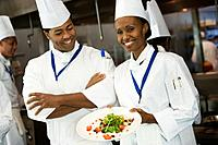 African female chef holding plate of food