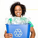 African woman holding recycling bin