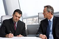 Multi_ethnic businessmen writing on paperwork