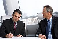 Multi_ethnic businessmen writing on paperwork