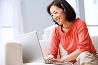 Asian woman typing on laptop
