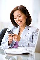 Asian businesswoman dialing cell phone