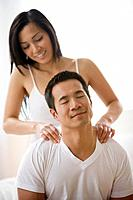 Asian woman massaging boyfriend's shoulders
