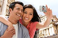 Asian couple taking own photograph (thumbnail)