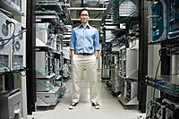 Asian man standing in computer server room