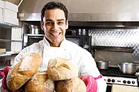 Hispanic male baker holding fresh bread