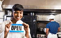 Mixed Race female chef holding Open sign in kitchen